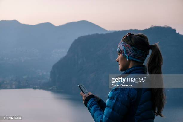 female hiker takes photo of mountain landscape with smart phone - padded jacket stock pictures, royalty-free photos & images