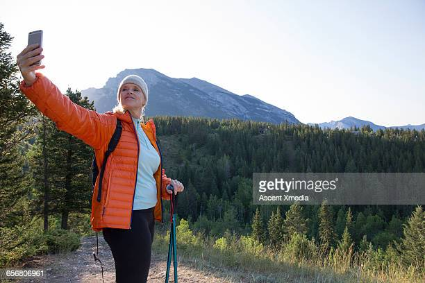 Female hiker takes selfie at edge of trail, mtns