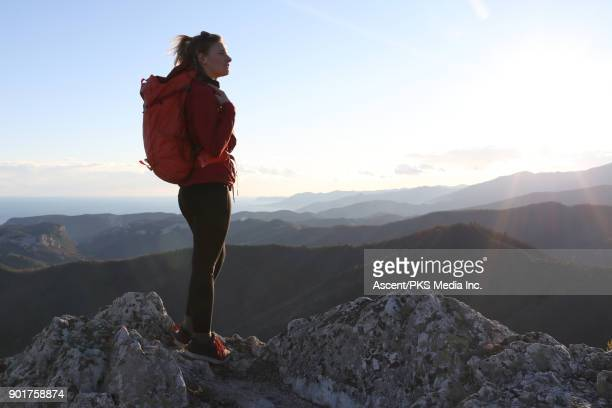 Female hiker traverses rock ridge, nears summit