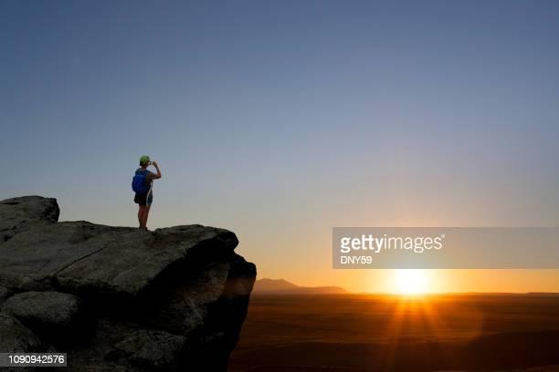 weibliche wanderer nutzt handy zum sonnenuntergang fotografieren - ganz oben stock-fotos und bilder