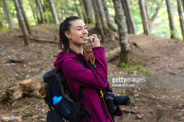 Female hiker using lip balm