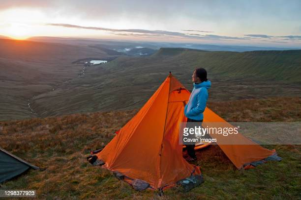 female hiker wakes up on pen y fan in wales - brecon beacons stock pictures, royalty-free photos & images