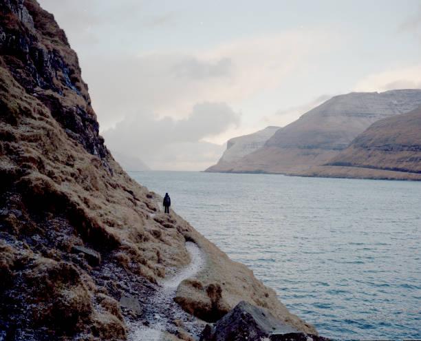 Female hiker walking along cliff in the Faroe Islands
