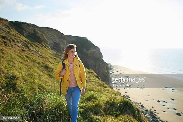 Female hiker walking along cliff top.