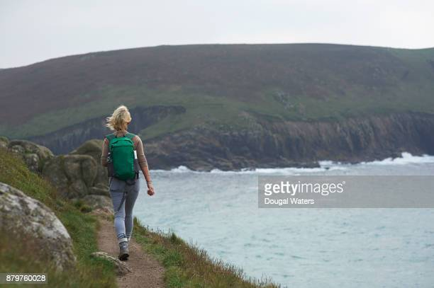 Female hiker walking along coastal path, UK.