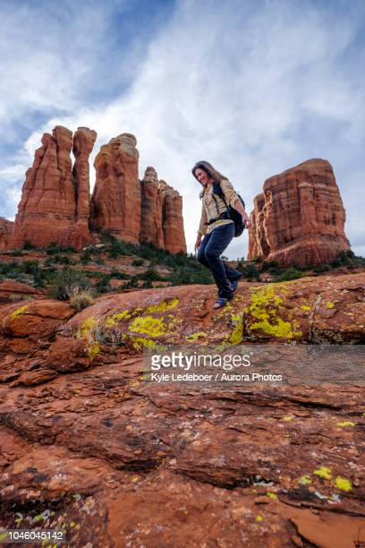 female hiker walking down rocks at cathedral rock, arizona, united states - sedona stock photos and pictures