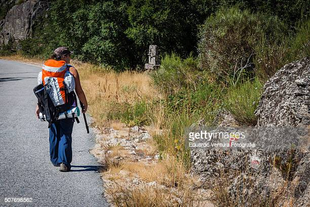 Female hiker walking down the road near Castro Laboreiro, PORTUGAL