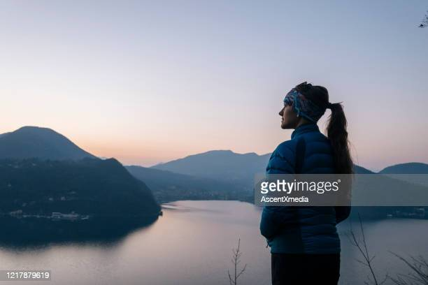 female hiker walks above lake and european alps - jacket stock pictures, royalty-free photos & images