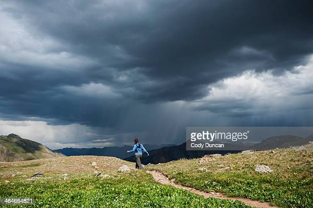 Female hiker walks along trail amid approaching rain in Ice Lakes Basin, San Juan mountains, Colorado, USA