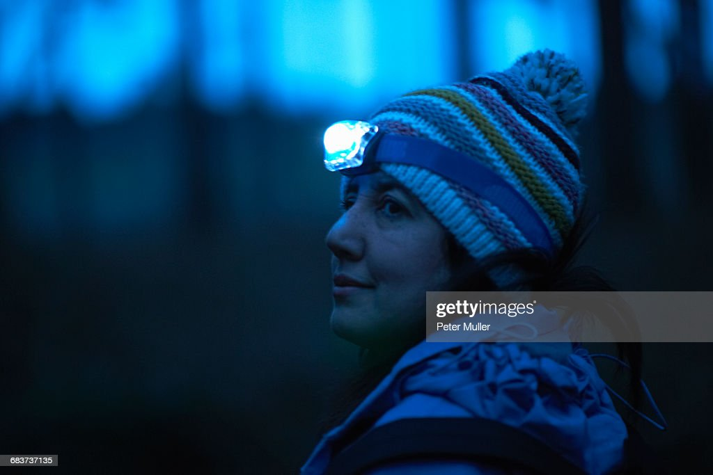 dd23230174d Female hiker wearing head torch looking over her shoulder from forest at  night   Stock Photo