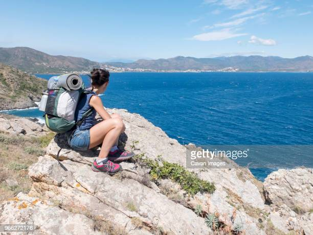 female hiker with backpack looking at view while sitting on rocks by sea against mountains during sunny day - gerona province stock photos and pictures