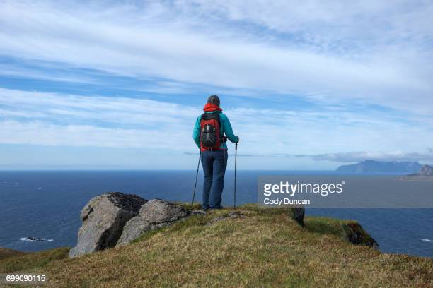 Female hiker with view over sea from Ytresandheia, Moskenesy, Lofoten Islands, Norway