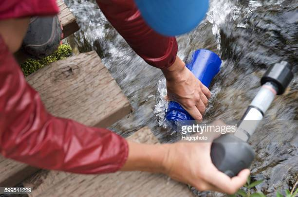 Female hiker with water filter filling water bottle in stream