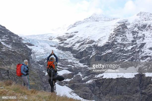 Female hikers pause on mountain slope after snowstorm