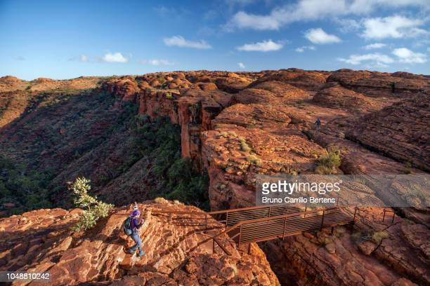 female hiking on the rim of king's canyon - northern territory australia stock photos and pictures
