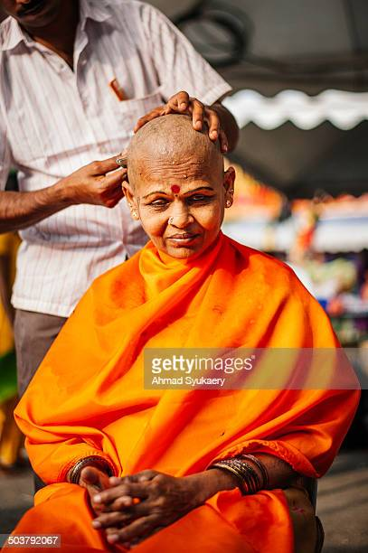 Female Hindu devotee having her hair shaved off as part of the cleansing ritual during Thaipusam festival at Batu Caves temple, Kuala Lumpur,...