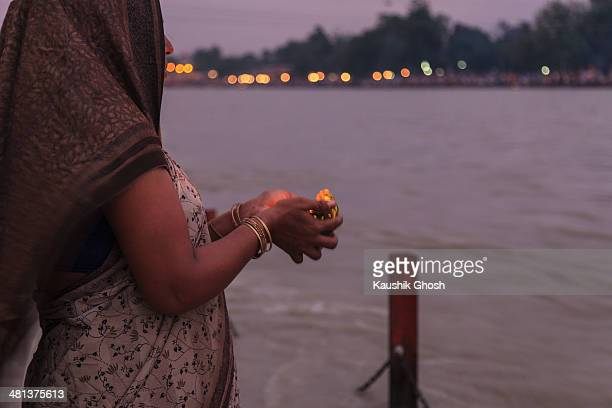 CONTENT] A female Hindu devotee is performing the evening ritual at the bank of Ganges in Haridwar
