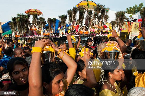 Female Hindu devotees carrying lotas with water during Thaipusam Festival at Batu Caves.