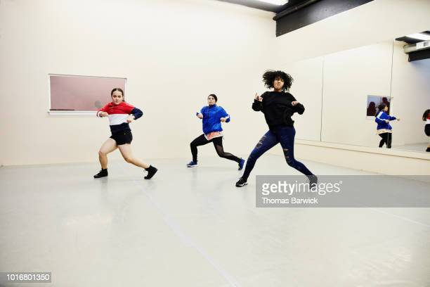 female hip hop dance group practicing in dance studio - dance troupe stock photos and pictures