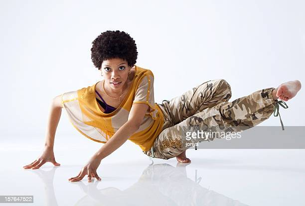 female hip hop dancer mid move with all white background - breakdancing stock photos and pictures