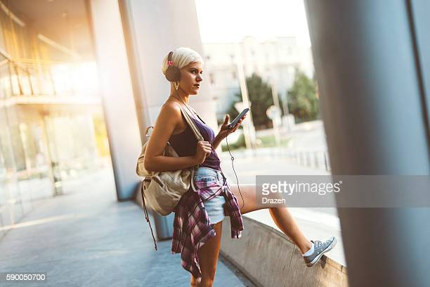 Female hipster in city downtown listening music on street
