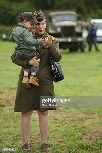 A female historical DDay reenactment enthusiast dressed as an American soldier walks with her son at a reenactment camp on June 4 2014 in Sainte Mere...