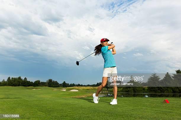 a female hitting a golf ball. - パットする ストックフォトと画像