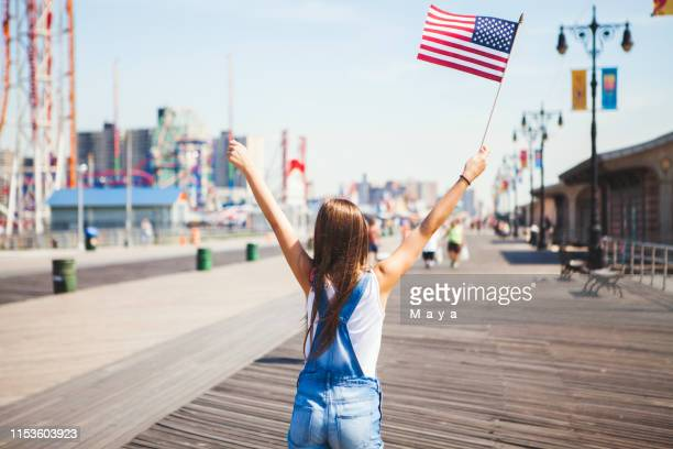 female holding american flag - fourth of july stock pictures, royalty-free photos & images