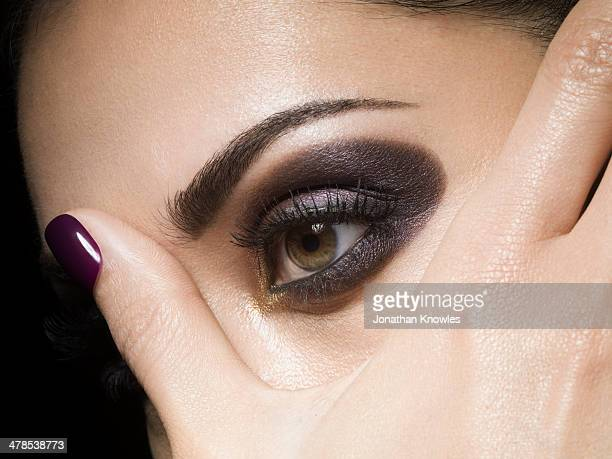 Female holding her fingers over one of her eyes