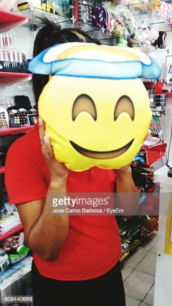 Female Holding Smiley Face While Standing In Store