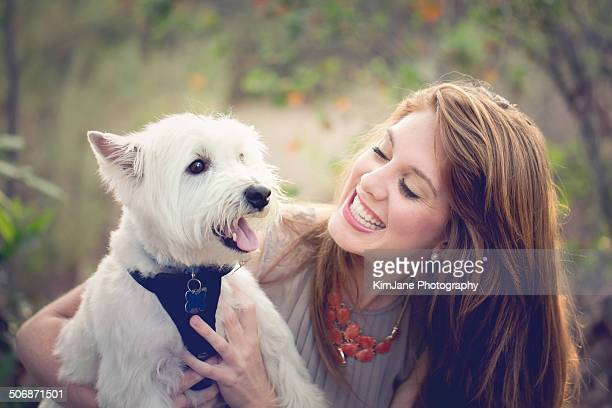 Female holding West Highland White Terrier