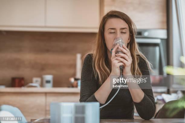 female holds a mask vapor inhaler - amigdalite imagens e fotografias de stock