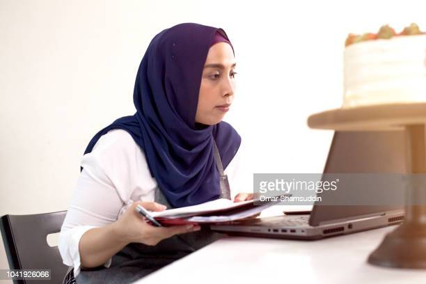 Female Home baker in hijab doing business with her laptop