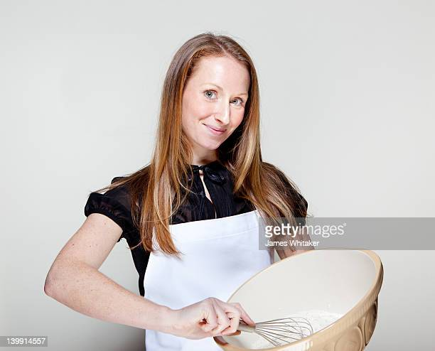 female home cook with mixing bowl - female whipping stock-fotos und bilder