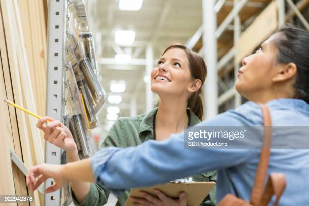 female home improvement employee assists customer - construction material stock pictures, royalty-free photos & images