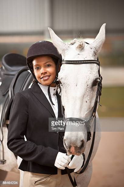 female horse rider standing by horse. - riding hat stock pictures, royalty-free photos & images