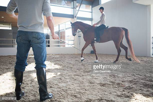 female horseback riding with instructor in indoor paddock - female whipping stock-fotos und bilder