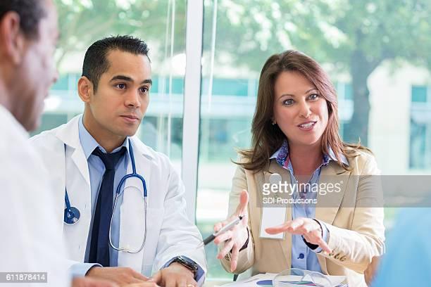 Female hospital executive meets with hospital staff