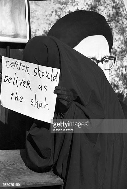 A female hostage taker in black chador holds a banner calling for president Jimmy Carter to deliver the Shah of Iran while standing in front of...