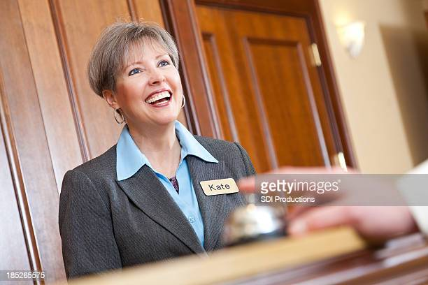 Female hotel manager behind a desk with guest ringing bell