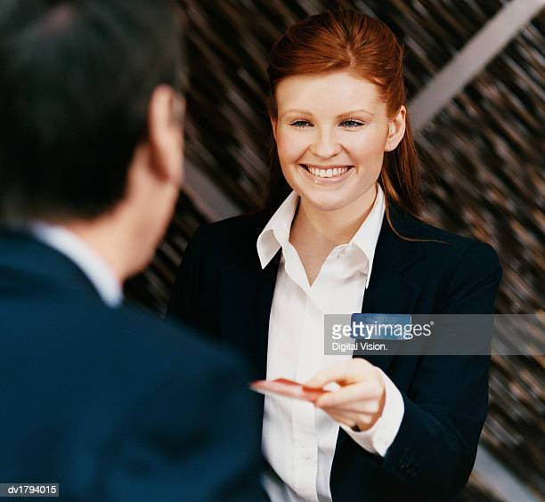female hotel receptionist hands a credit card to a customer - nameplate stock pictures, royalty-free photos & images
