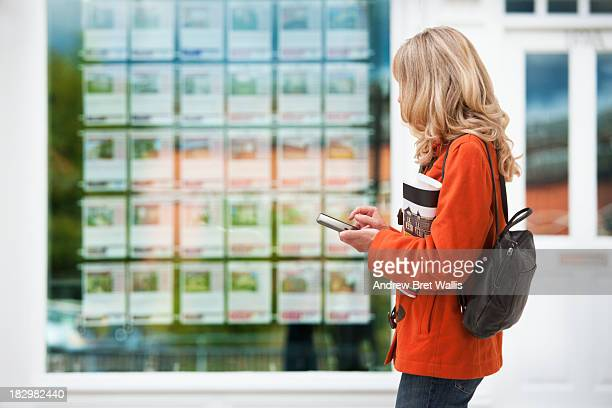 Female house buyer outside estate agents window