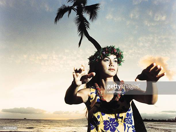 A female hula dancing outdoors near the ocean at sunset