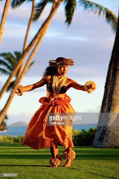 A female hula dancing outdoors near the ocean at sunset. She is wearing a Hawaiian hula skirt, a shell lei, and a Maile headband.