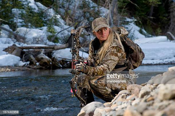 female hunter kneeling by a pile of rocks - hunting sport stock pictures, royalty-free photos & images