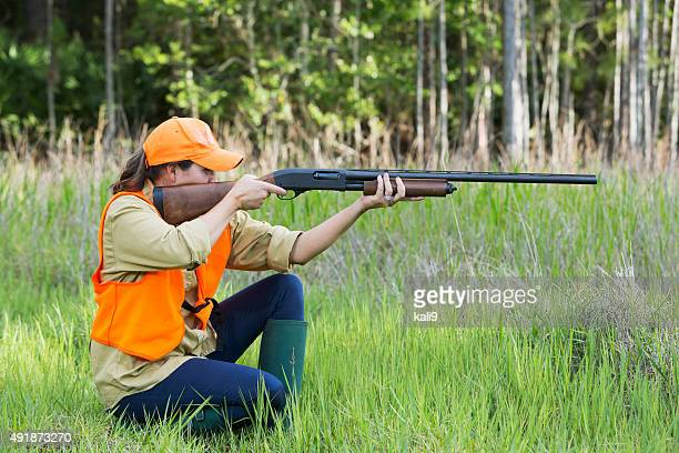 Female hunter with shotgun kneeling in tall grass