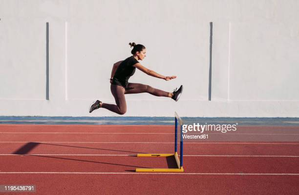 female hurdler during training on tartan track - athlete stock pictures, royalty-free photos & images