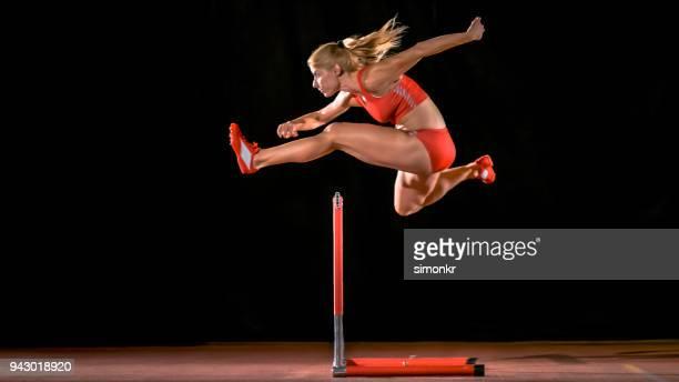 Female hurdler jumping over hurdle