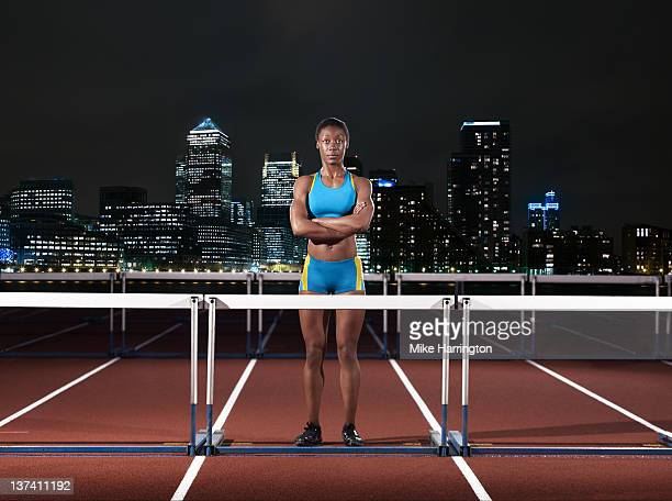 female hurdler standing on track in london - womens track stock photos and pictures