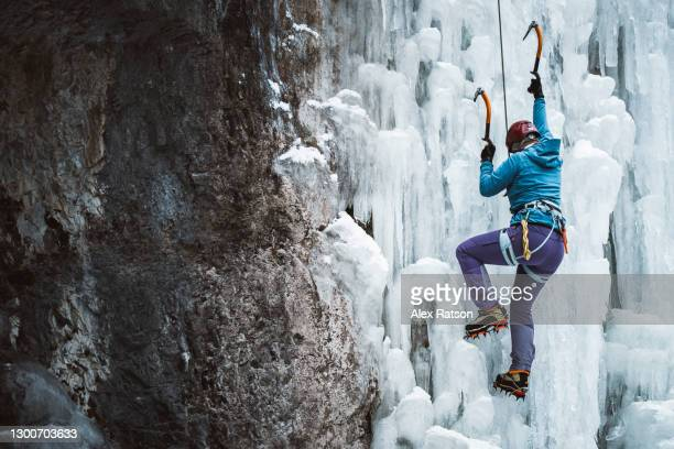 female ice climber ascends a steep frozen waterfall with dramatic light - image stock pictures, royalty-free photos & images